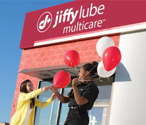 Employee giving balloons to child