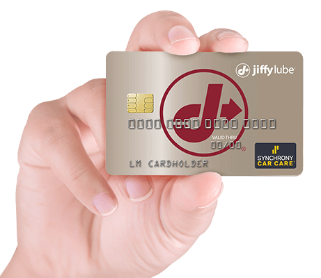 Hand holding a golden Jiffy Lube credit card that offers flexible financing
