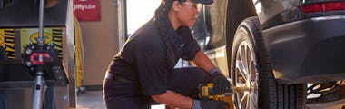 jiffy lube employee completing a tire rotation
