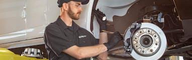 jiffy lube employee inspecting a vehicle's anti lock brake