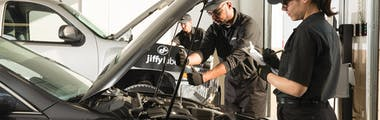 Two Jiffy Lube technicians going through a vehicle inspection checklist