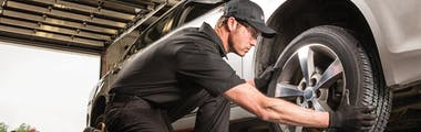 Jiffy Lube technician wearing all black uniform replacing a tire after balancing the wheel