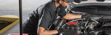Jiffy Lube technician adding transmission fluid to a silver vehicle