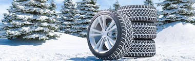 Digitized picture of stacked winter tires with another tire leaning against them in front of pine trees