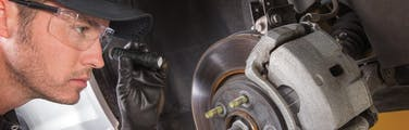 A Jiffy Lube technician inspecting a vehicle brake rotor & brakes pads with small flashlight