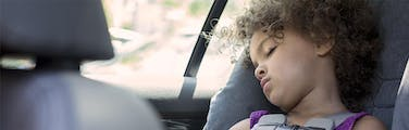 Curly haired child sleeping in a car seat while on a holiday road trip
