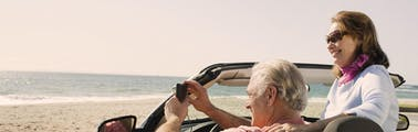 Elderly couple on a road trip in a convertible with the top down taking pictures of the ocean in the summer sun