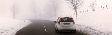White vehicle driving safely on winter roads covered in snow