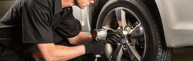 Jiffy Lube technician using an impact wrench to tighten lug nuts on a new tire