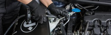 Jiffy Lube technician topping off windshield wiper fluid during an auto service