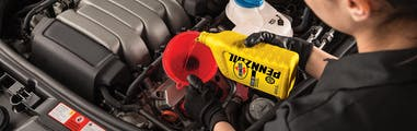 Jiffy Lube technician conducting an oil change by adding Pennzoil motor oil into the engine oil reserve